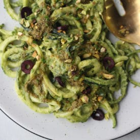 Zucchini noodles in creamy green sauce on a white plate.