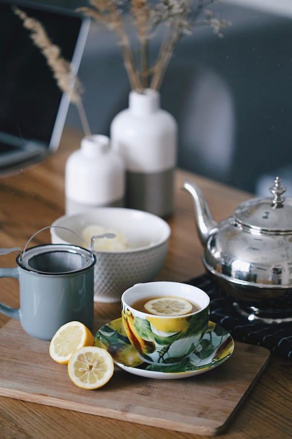 Mug of tea with lemon next to teapot.