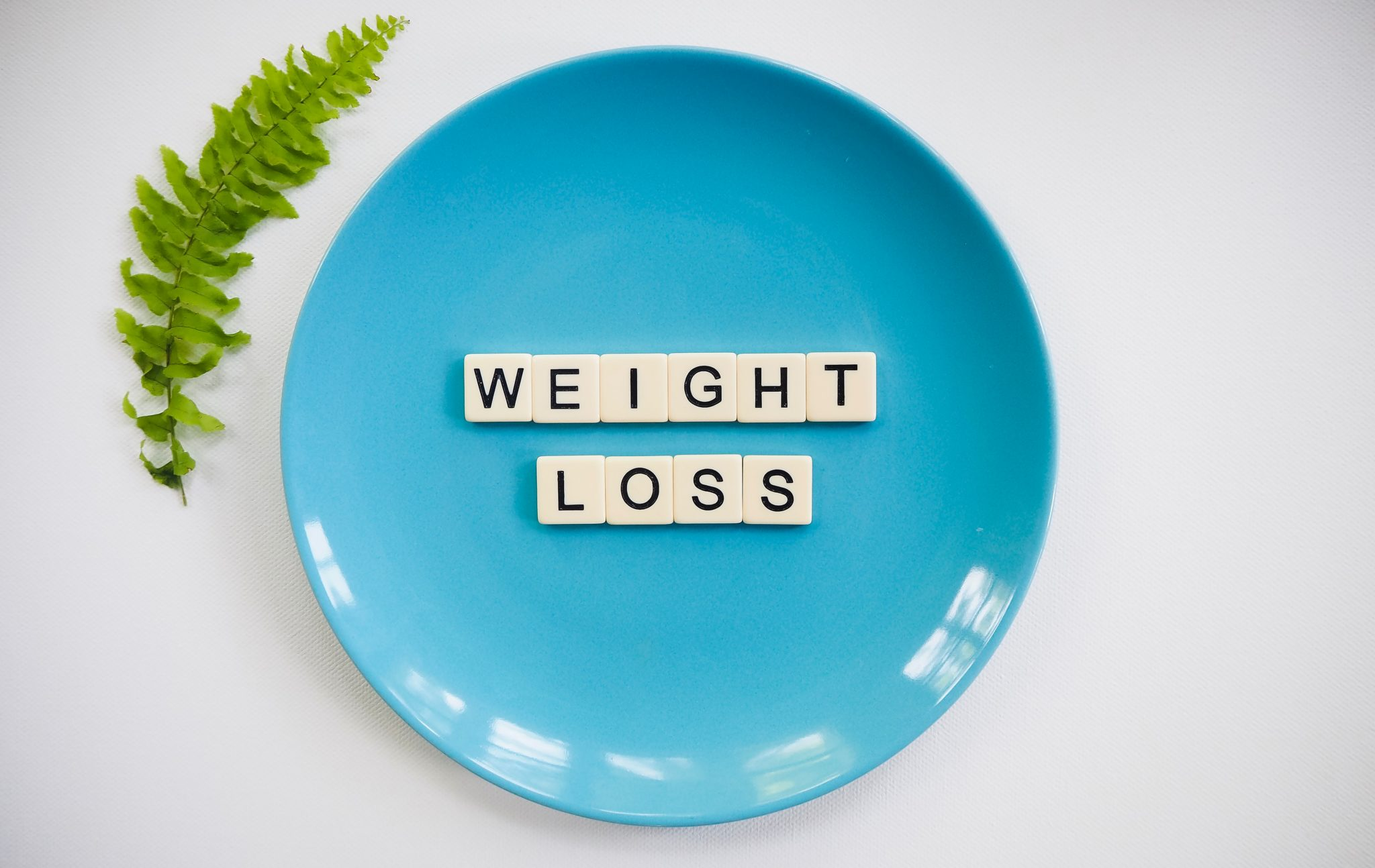 "blue plate with tiles that spell ""weight loss"" against a white background"