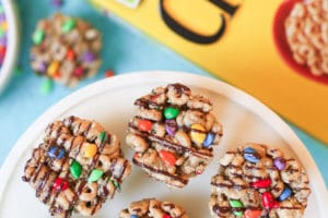 birds eye view of kid friendly no bake cheerios bars garnished with chocolate drizzle on a white plate with a box of cheerios in the background