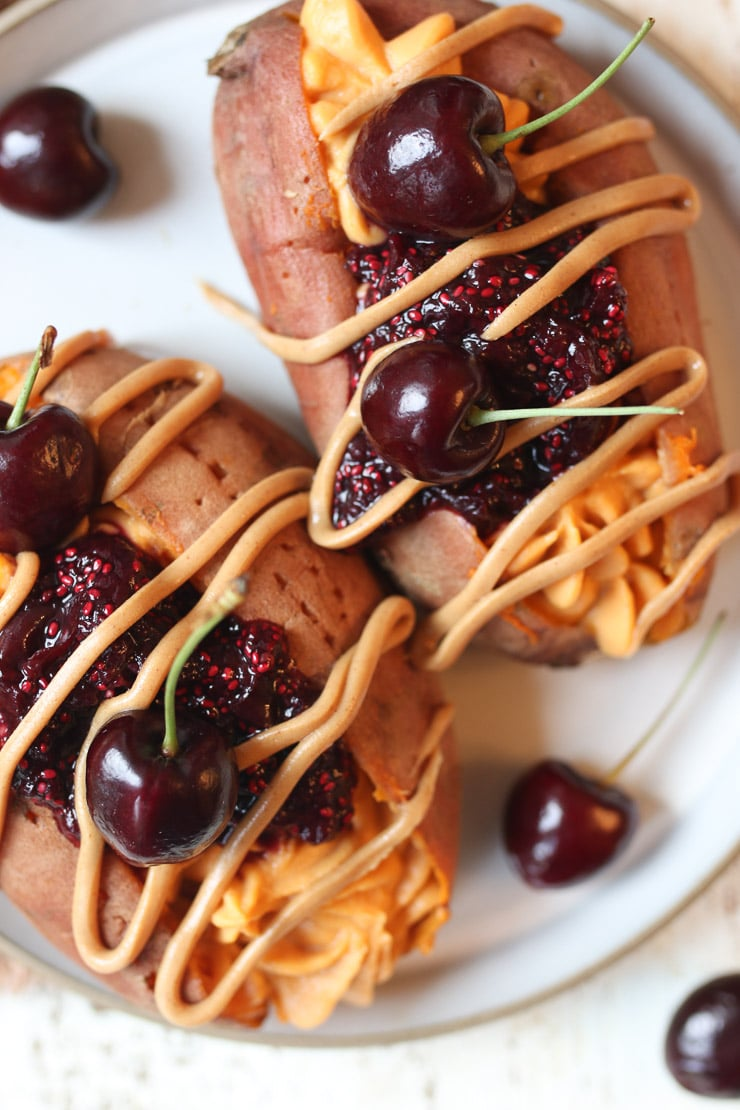 Stuffed sweet potato on a plate drizzled with peanut butter and topped with chia jam and cherries