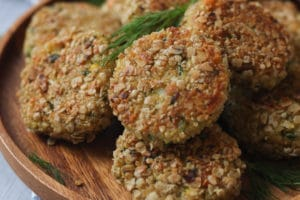 close up image of gluten free and child friendly quinoa fish cakes garnished with fresh herbs on a wooden plate