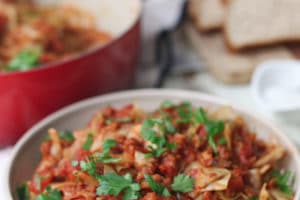 close up image of vegan low carb and gluten free unstuffed cabbage rolls in a bowl garnished with fresh parsley