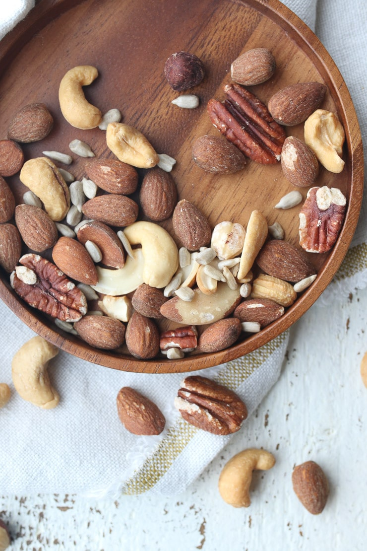 mixed nuts on a wooden plate as part of a heart healthy diet