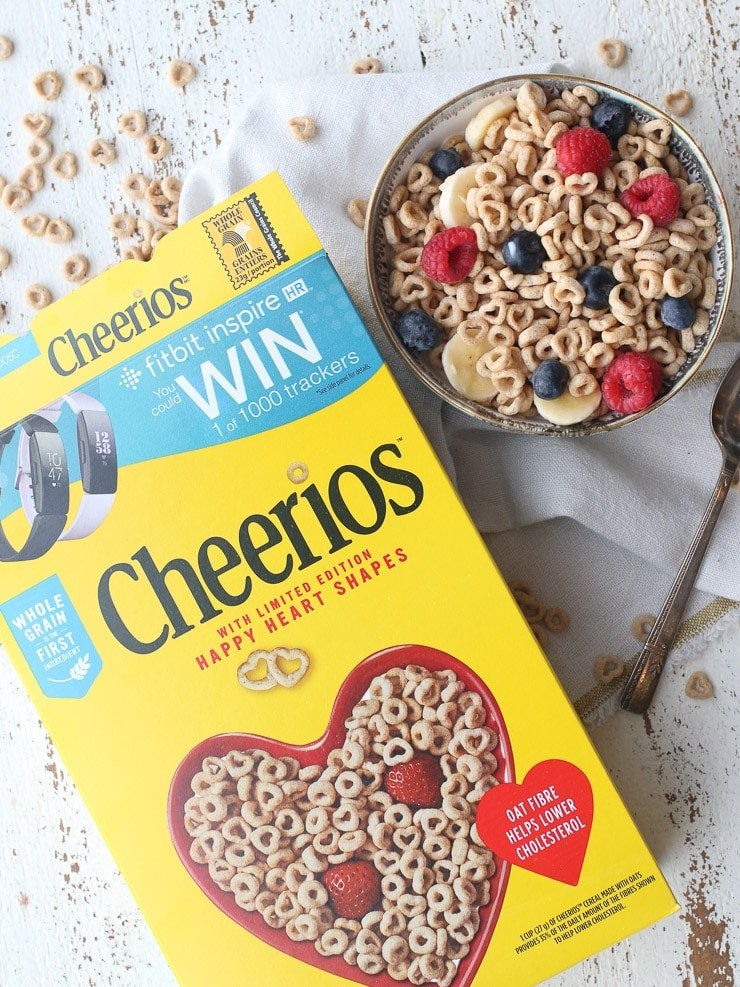 birds eye view of cheerios box and bowl of cheerios with berries essential for a heart healthy diet