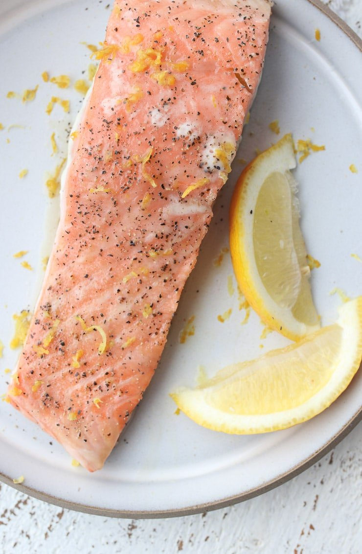 pink salmon on a white plate garnished with lemon zest