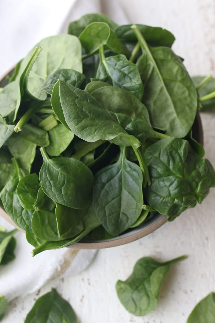 birds eye view of leafy greens in a white bowl for heart healthy