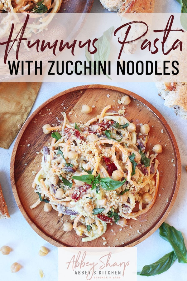 pinterest image of vegan hummus pasta with zucchini noodles on a wooden plate garnished with basil with text overlay