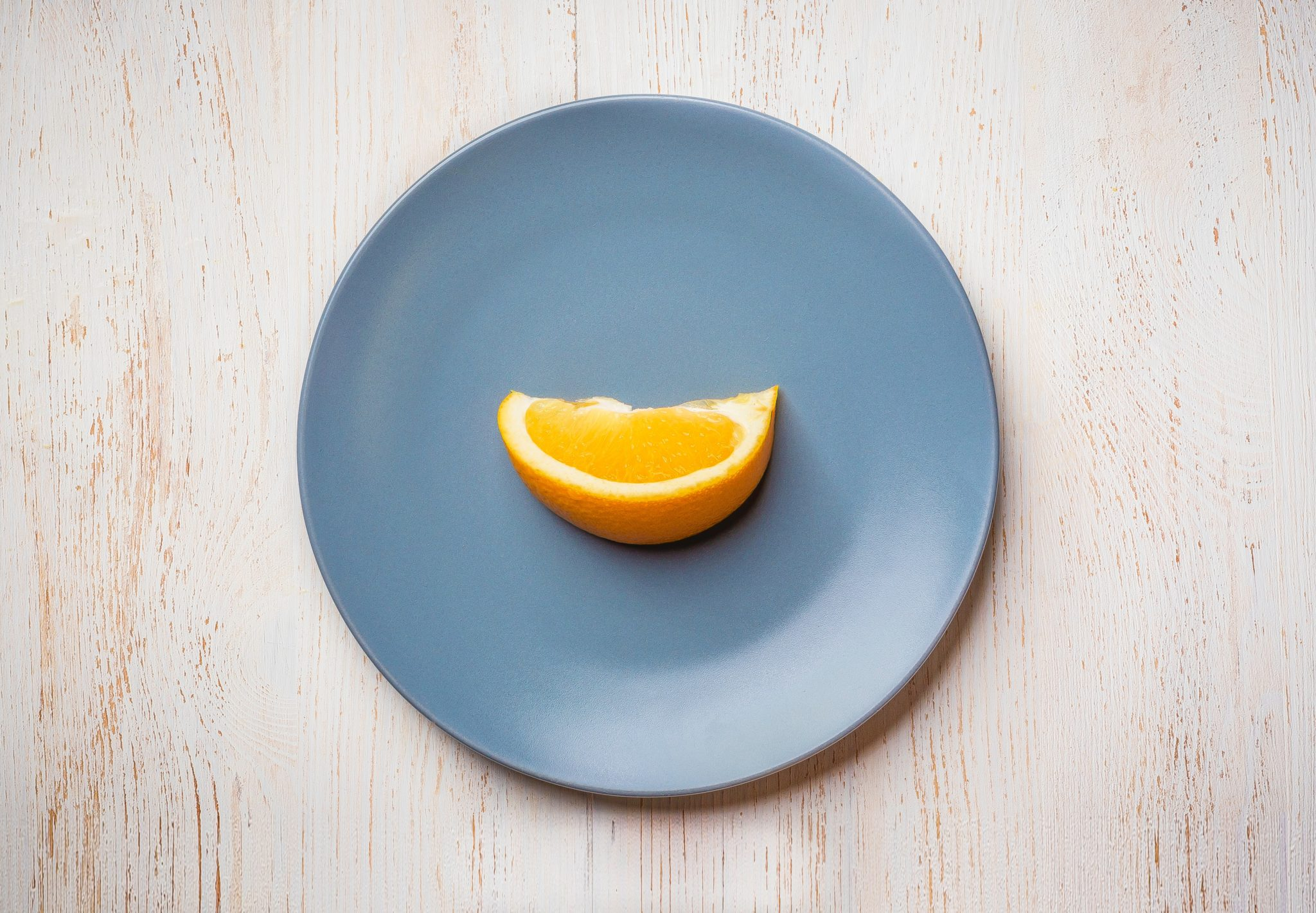 birds eye view of a blue plate with a single orange slice on it against a light background