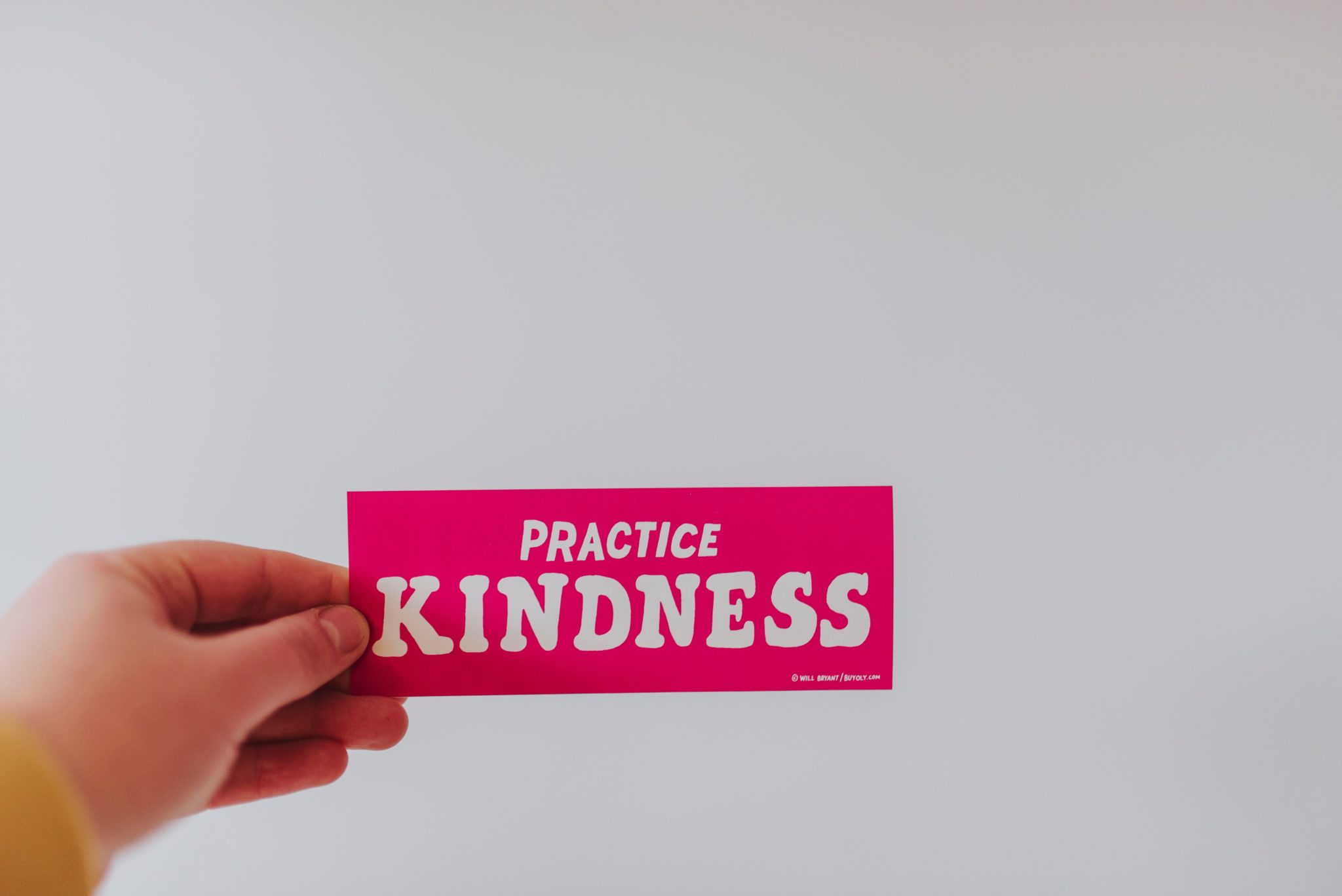 "person holding pin sign that says ""practice kindness"" as a way to challenge food police"