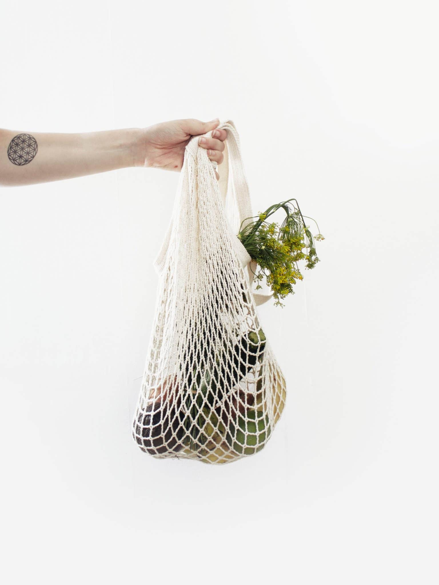 person carrying a reusable grocery bag with produce