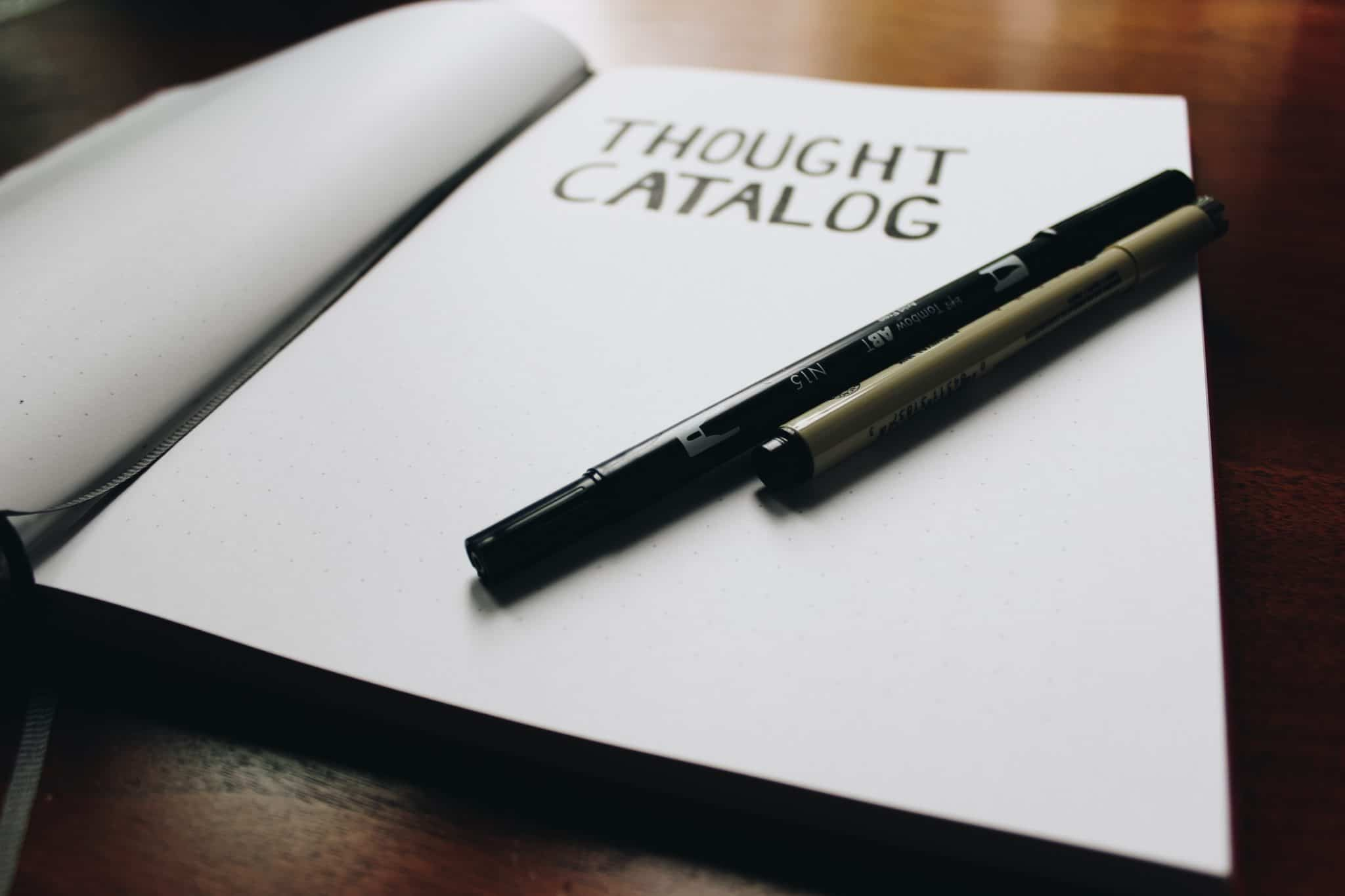 "notebook open on a table that reads ""thought catalog"" next to a black pen"
