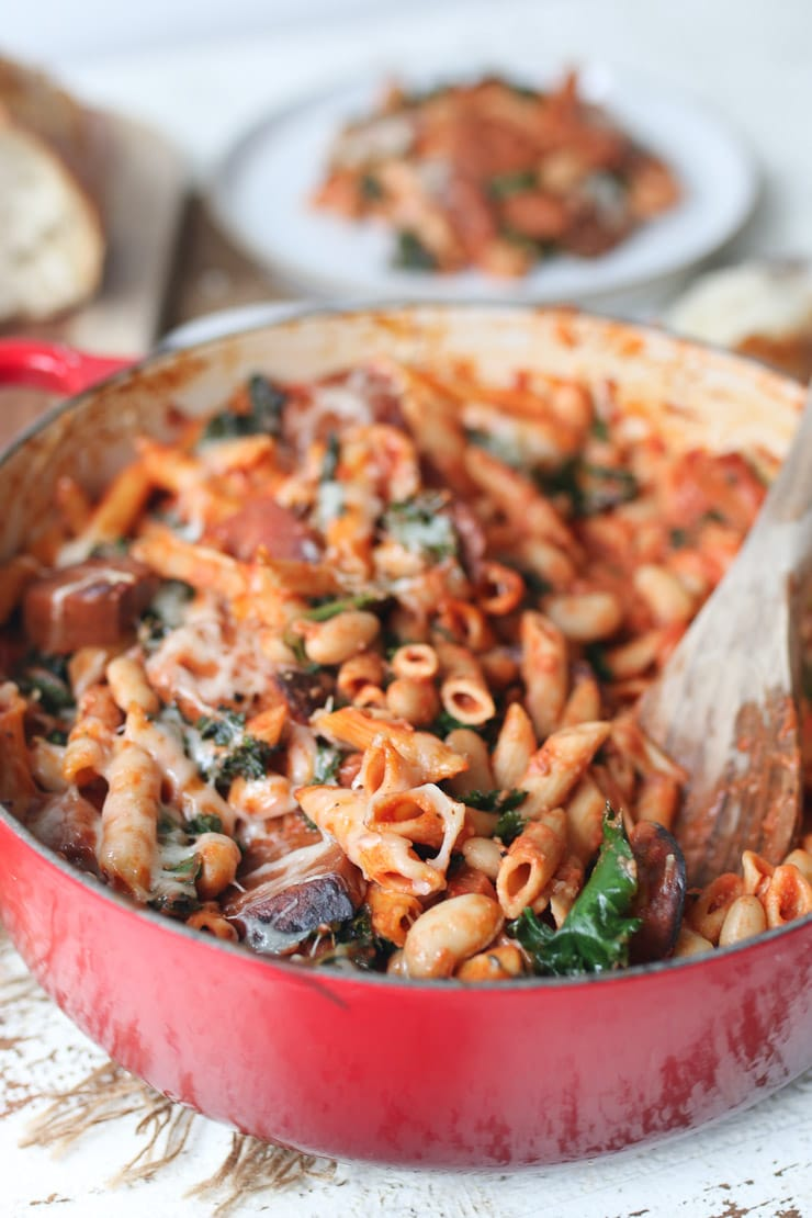 Pasta bake in red casserole dish with wooden spoon in the middle