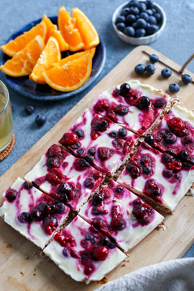 birds eye view of pantry staples frozen yogurt breakfast bars garnished with berries served on a wooden surface next to fresh orange slices
