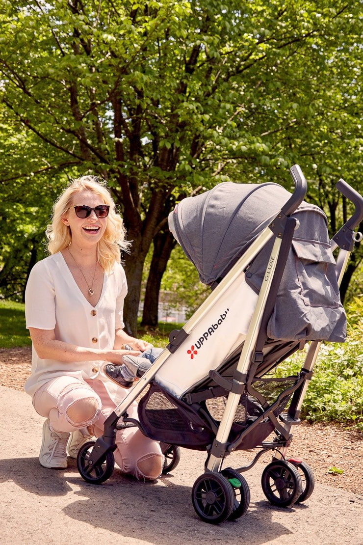 abbey outside in a white blouse with baby e in a stroller as a fun outdoor activity
