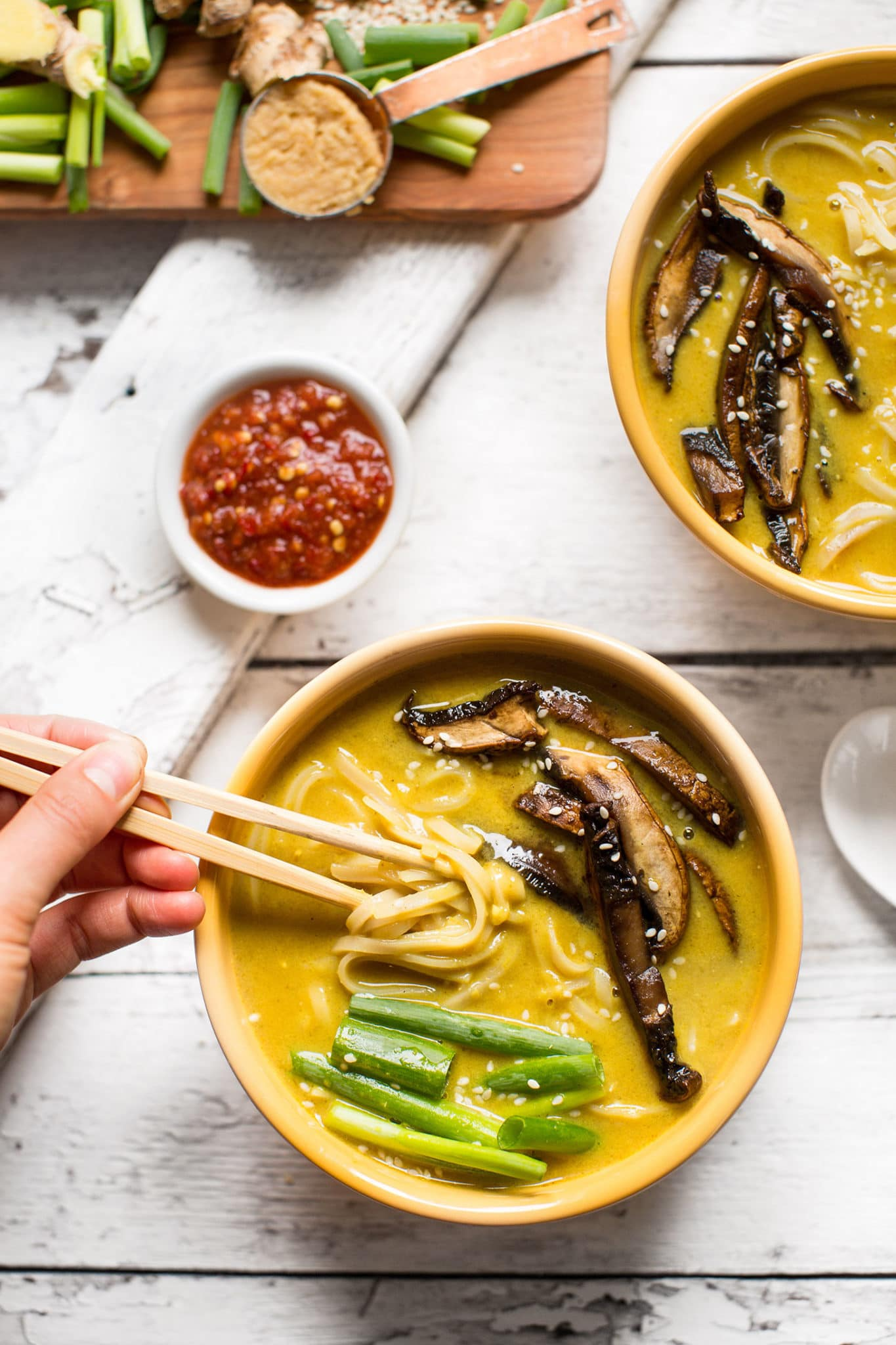 a cream bowl of coconut curry ramen with mushrooms and green onions on top with a pair of chopsticks lifting out some noodles.