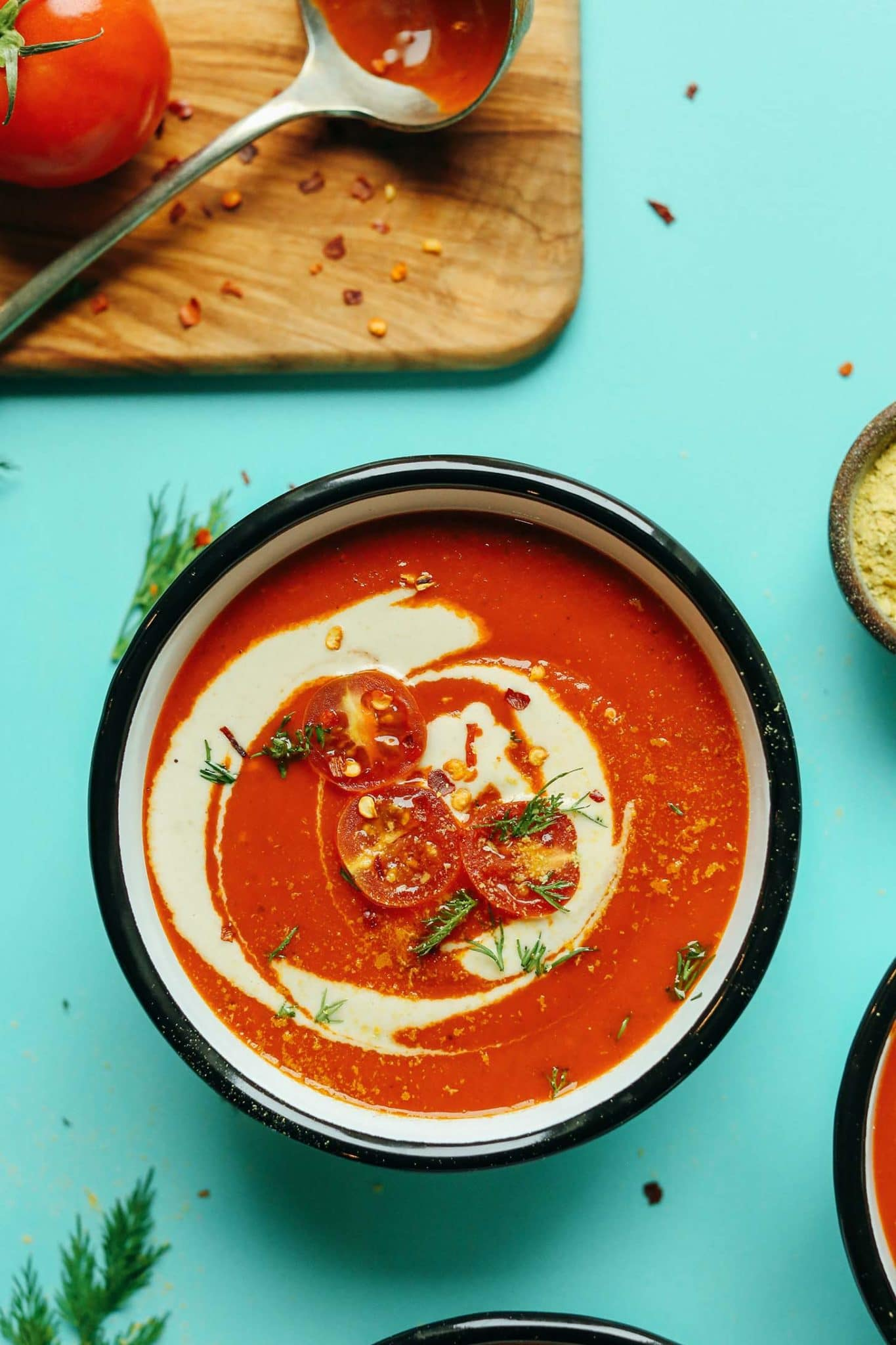 a bowl of creamy roasted red pepper tomato soup topped with tomatoes and greens on a teal background.
