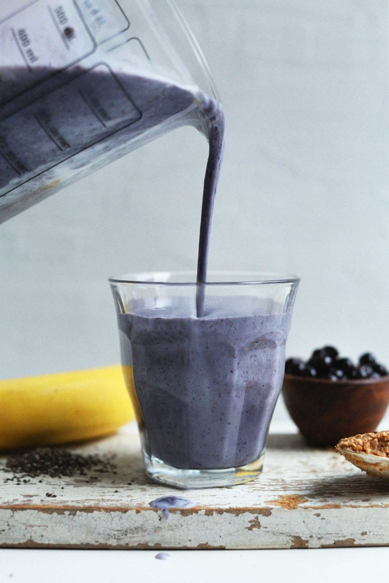 close up of blueberry almond butter smoothie being poured from a blender into a clear glass with a fresh banana and blueberries in the background