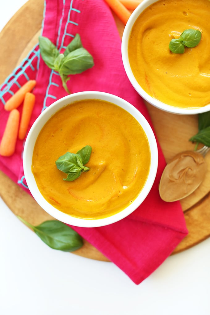 birds eye view of creamy pantry staple thai carrot soup garnished with fresh herbs served on a wooden surface next to fresh carrots and nut butter