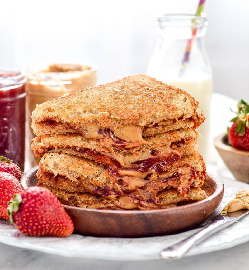 close up of grilled peanut butter and jelly sandwich halves stacked on a plate next to jars of peanut butter and jelly with a glass of milk and fresh strawberries in the background