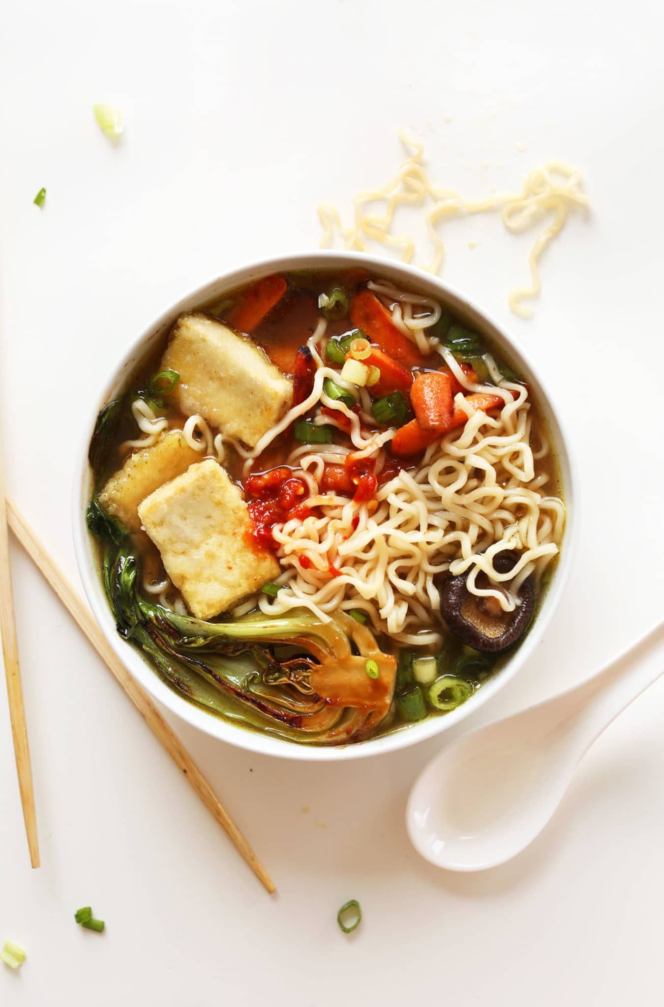 A bowl vegan ramen with tofu, bok choy, and green onions on top on a white background.