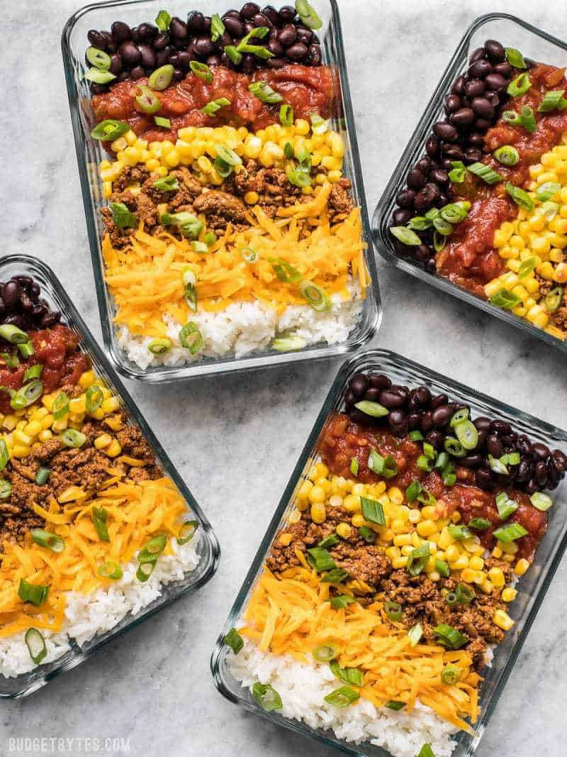 birds eye view of four pantry staple burrito bowls garnished with green onions