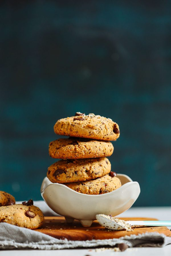 close up image of a stack of pantry staple trail mix cookies in a white bowl against a dark background