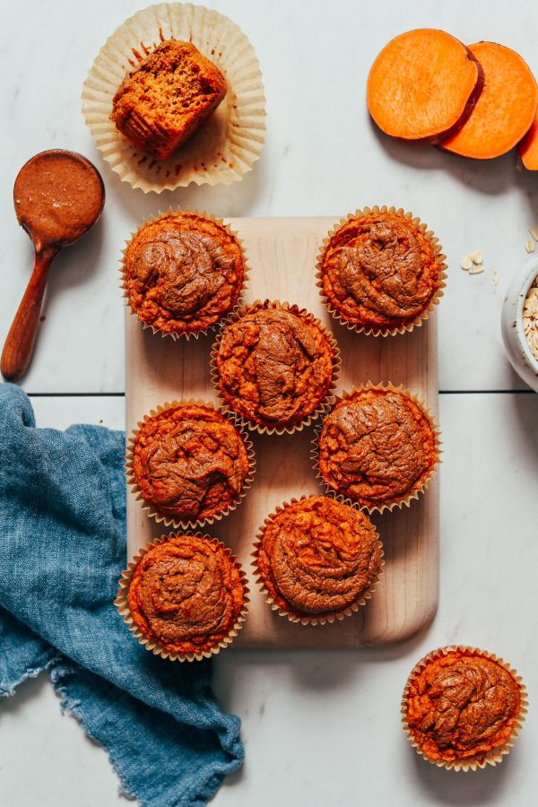 birds eye view of multiple almond butter sweet potato muffins for social isolation on a wooden surface next to sweet potato slices and a spoon of almond butter