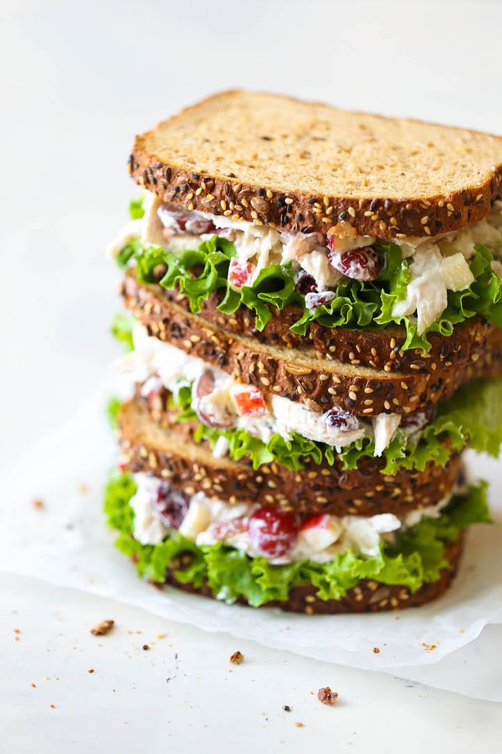 close up of two chicken salad sandwiches on brown bread stacked on top of one another on a white counter top