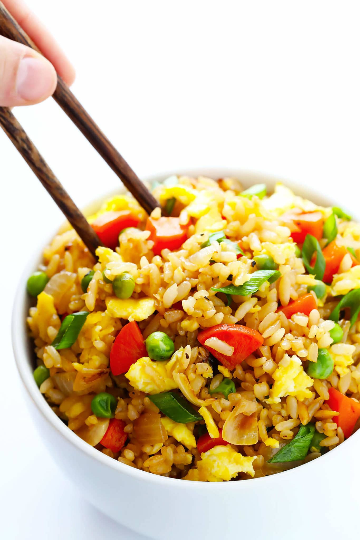 close up of pantry staple fried rice garnished with green onions served in a white bowl with brown chopsticks
