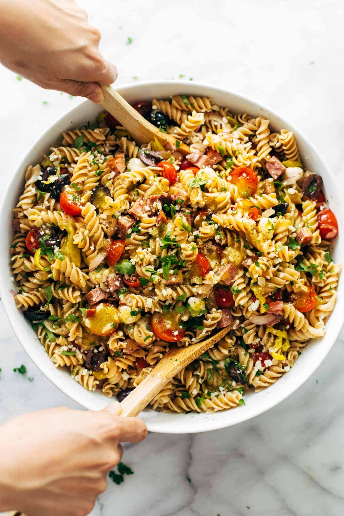 birds eye view of pantry staple quick and easy pasta salad served in a white bowl with wooden serving spoons