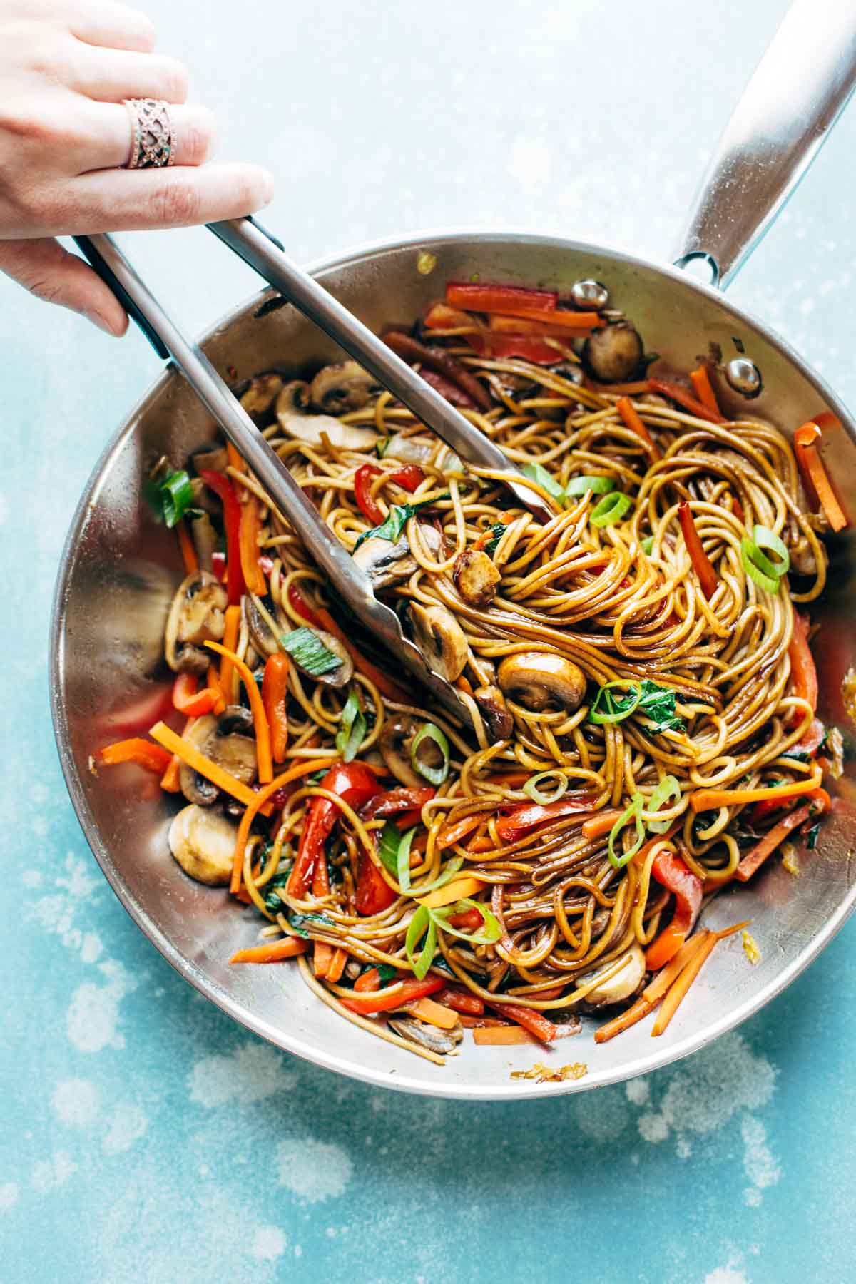 birds eye view of a large silver cooking pan containing fifteen minute lo mein using beans and pulses with tongs inside stirring the noodles