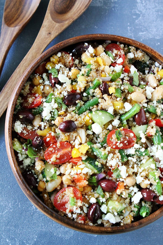 close up of a wooden bowl containing three bean mediterranean quinoa salad garnished with crumbled cheese next to two wooden serving utensils