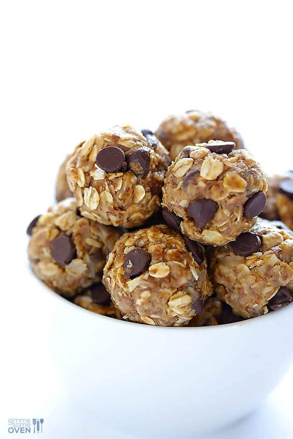 close up of multiple no bake energy bites garnished with chocolate chips in a white bowl
