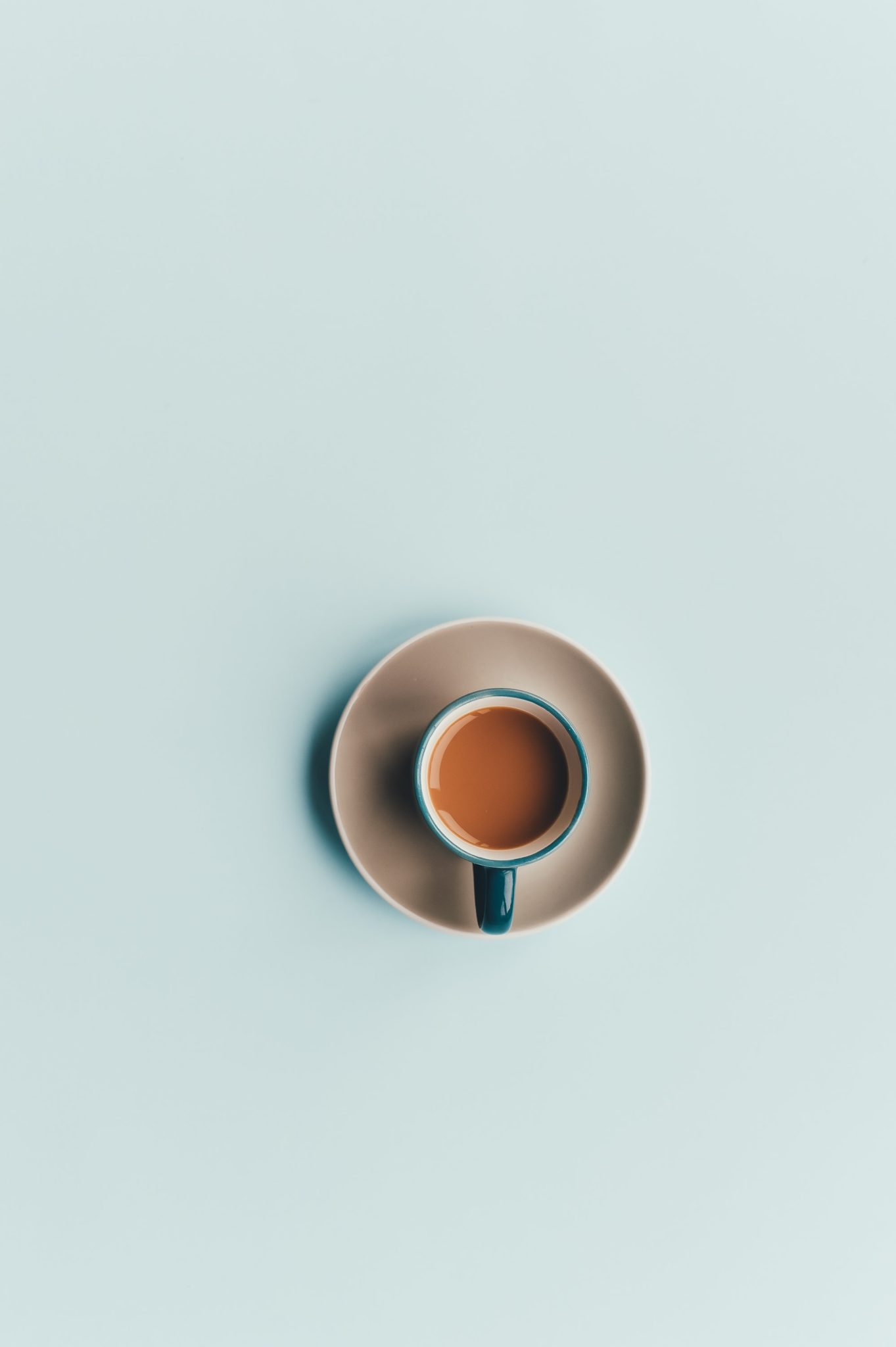 coffee in a blue mug on a saucer with a light blue background