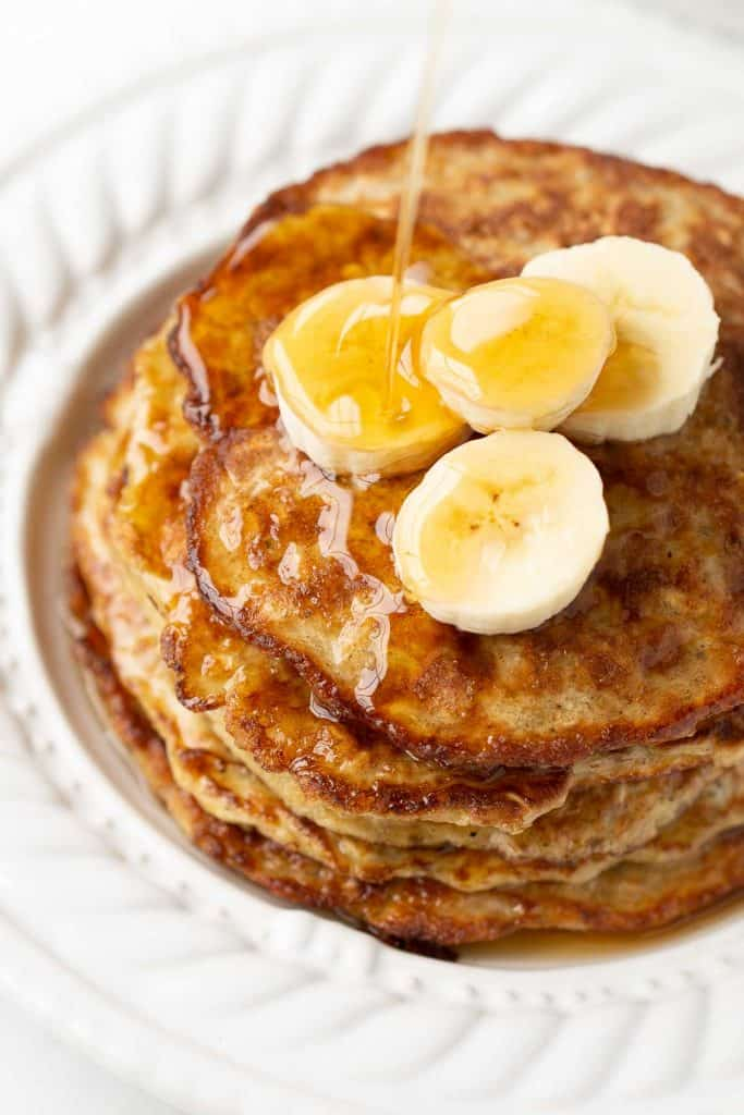 close up of a stack of pantry oatmeal pancakes garnished with banana slices drizzled with maple syrup