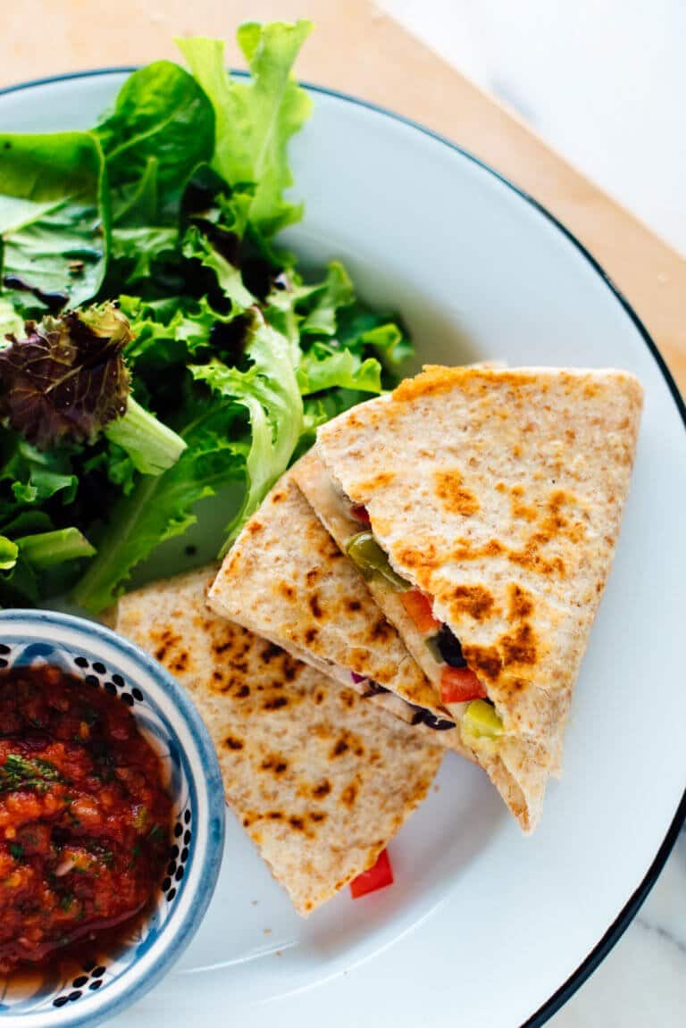 birds eye view of quick pantry staple quesadilla recipe served with greens and a small bowl containing salsa on a white plate