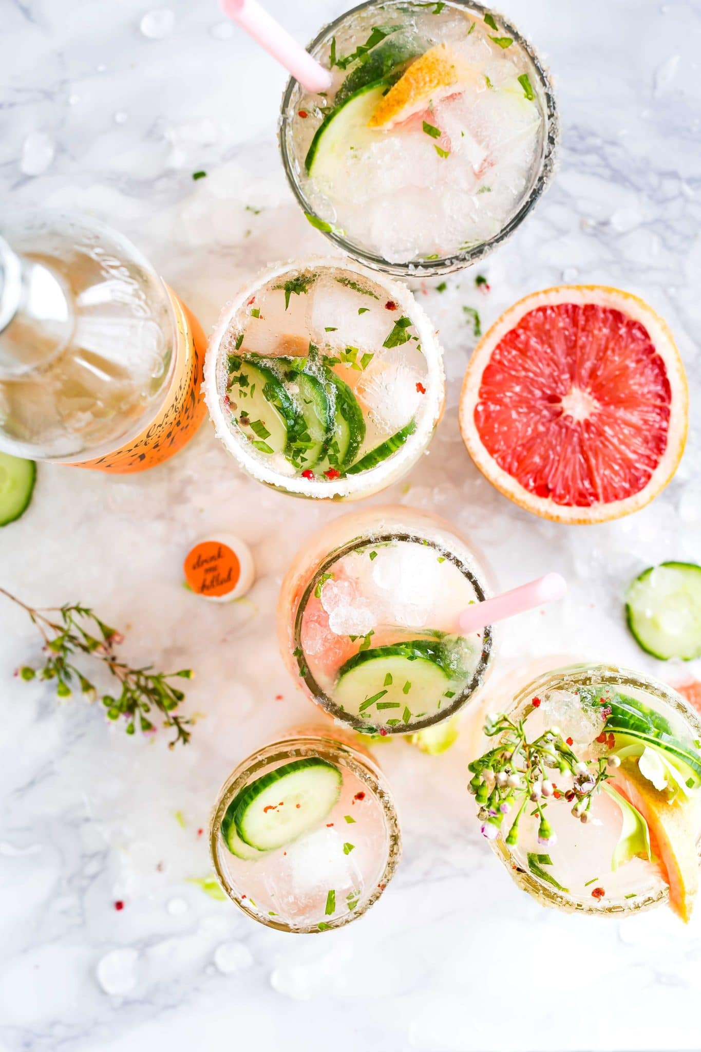 birds eye image of multiple cocktails garnished with fresh herbs, cucumbers, and grapefruit against a white marble background