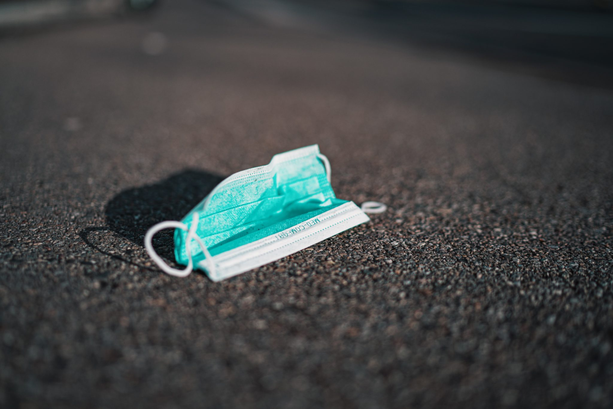 image of a blue surgical mask for coronavirus lying on the ground