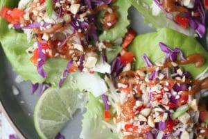 birds eye shot of no cook chicken lettuce wraps with peanut sauce served on a grey plate garnished with fresh lime wedges and chopped peanuts
