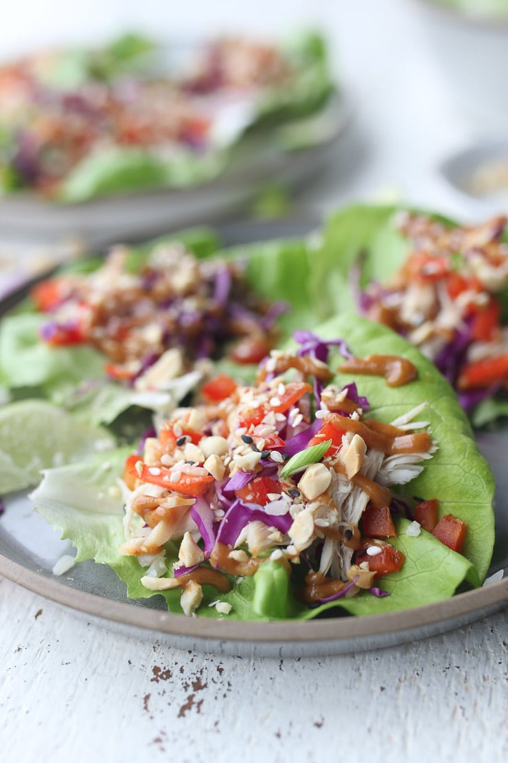 three chicken lettuce wraps on a grey plate topped with green onion