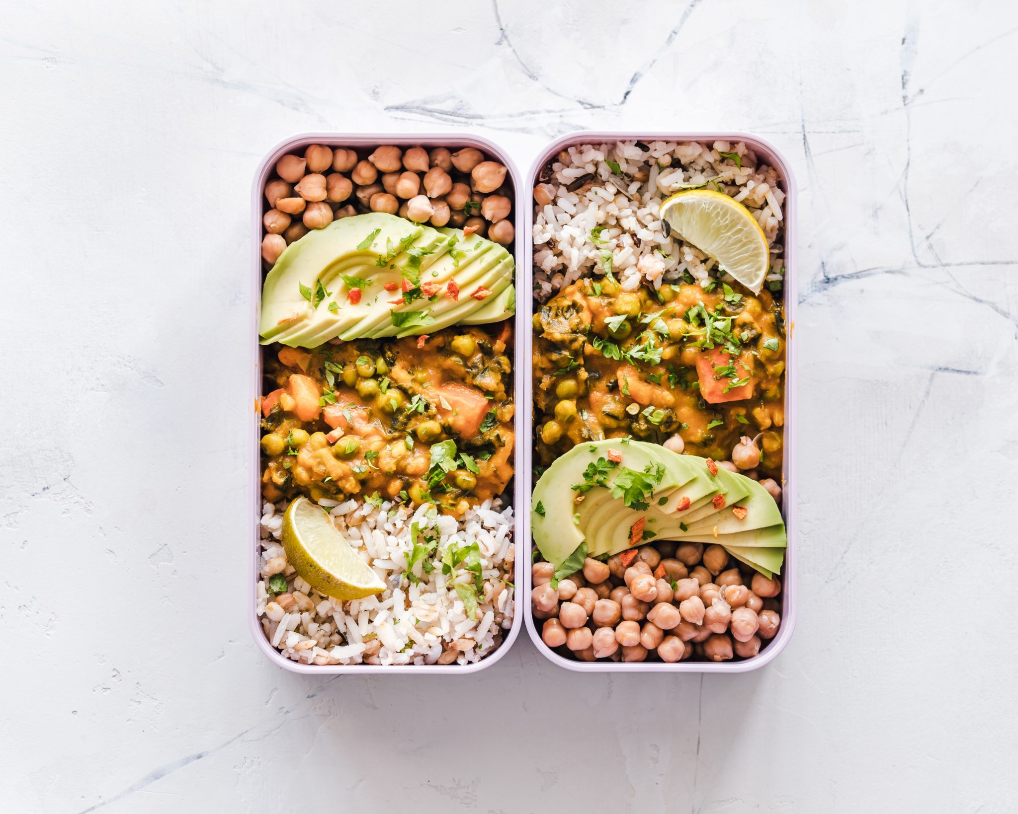 birds eye view of healthy meal prepped food in rectangular containers against a marble background