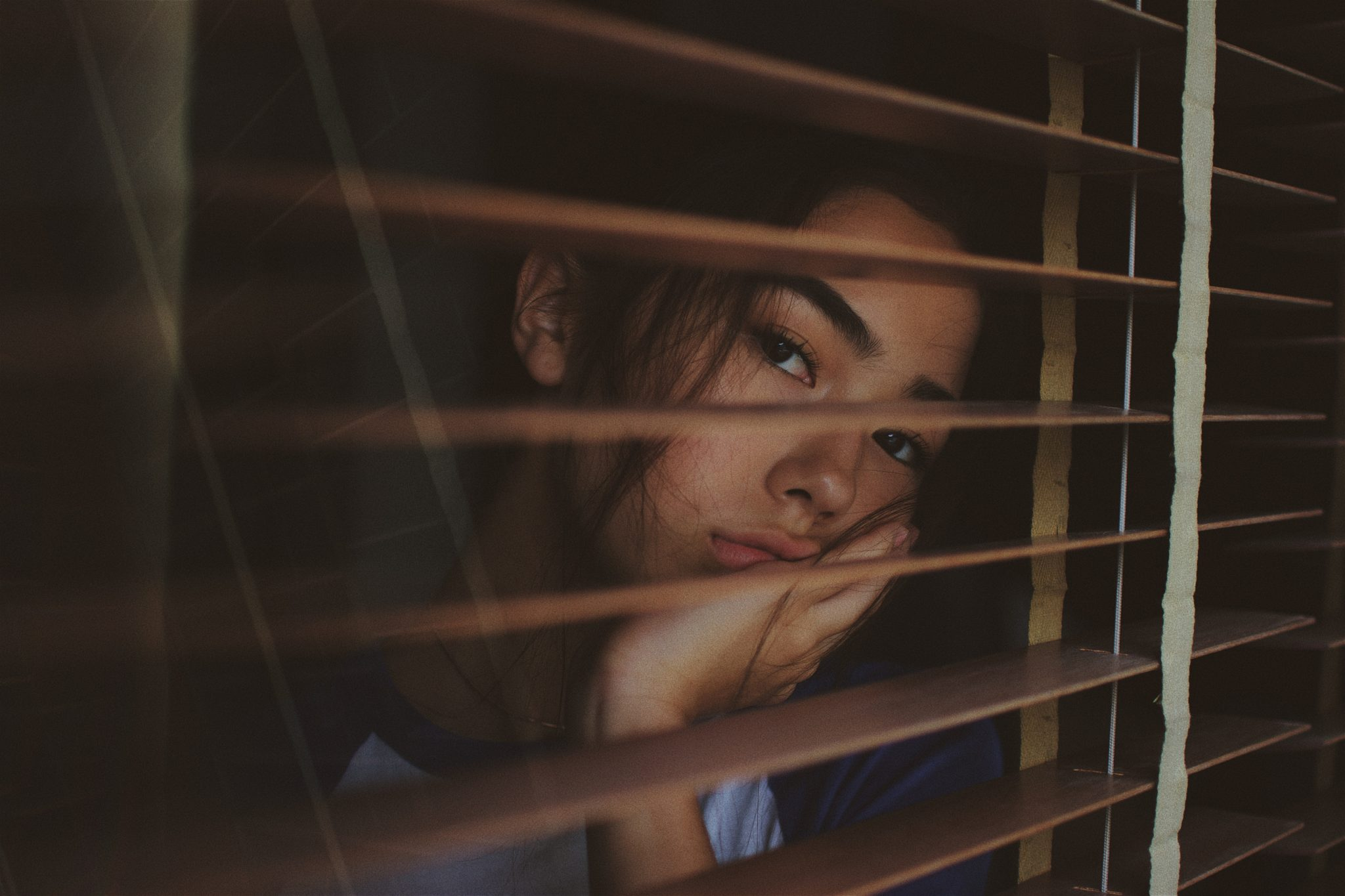 woman looking out the window during coronavirus isolation
