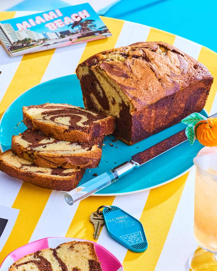 full shot of chocolate marble cake on a blue plate sitting on a yellow and white table