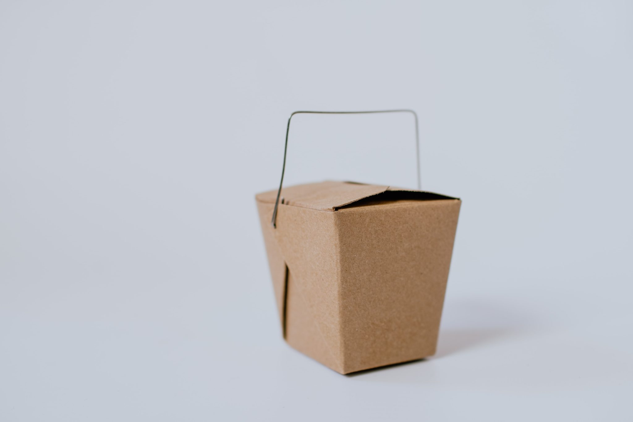 image of a brown take out box against a light grey background