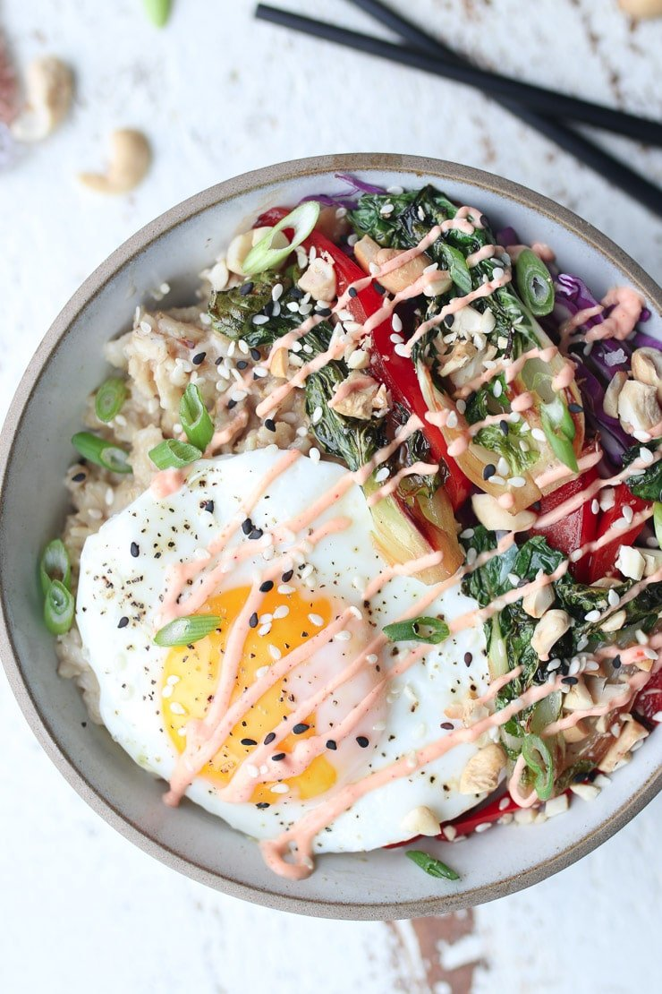 birds eye view of pantry staple savoury korean oatmeal bowl garnished with sesame seeds, spicy sauce, and green onions in a grey bowl
