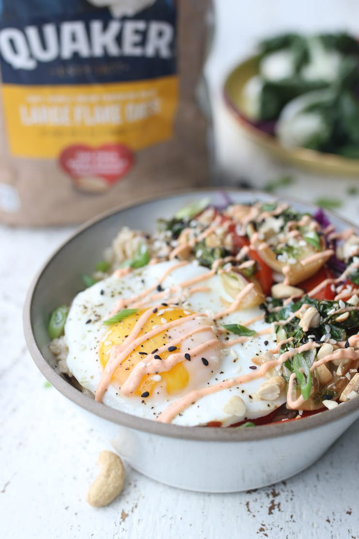 full shot image korean spiced savoury oatmeal bowl topped with spicy sauce, green onions, and sesame seeds in a grey bowl with a package of quaker oats in the background