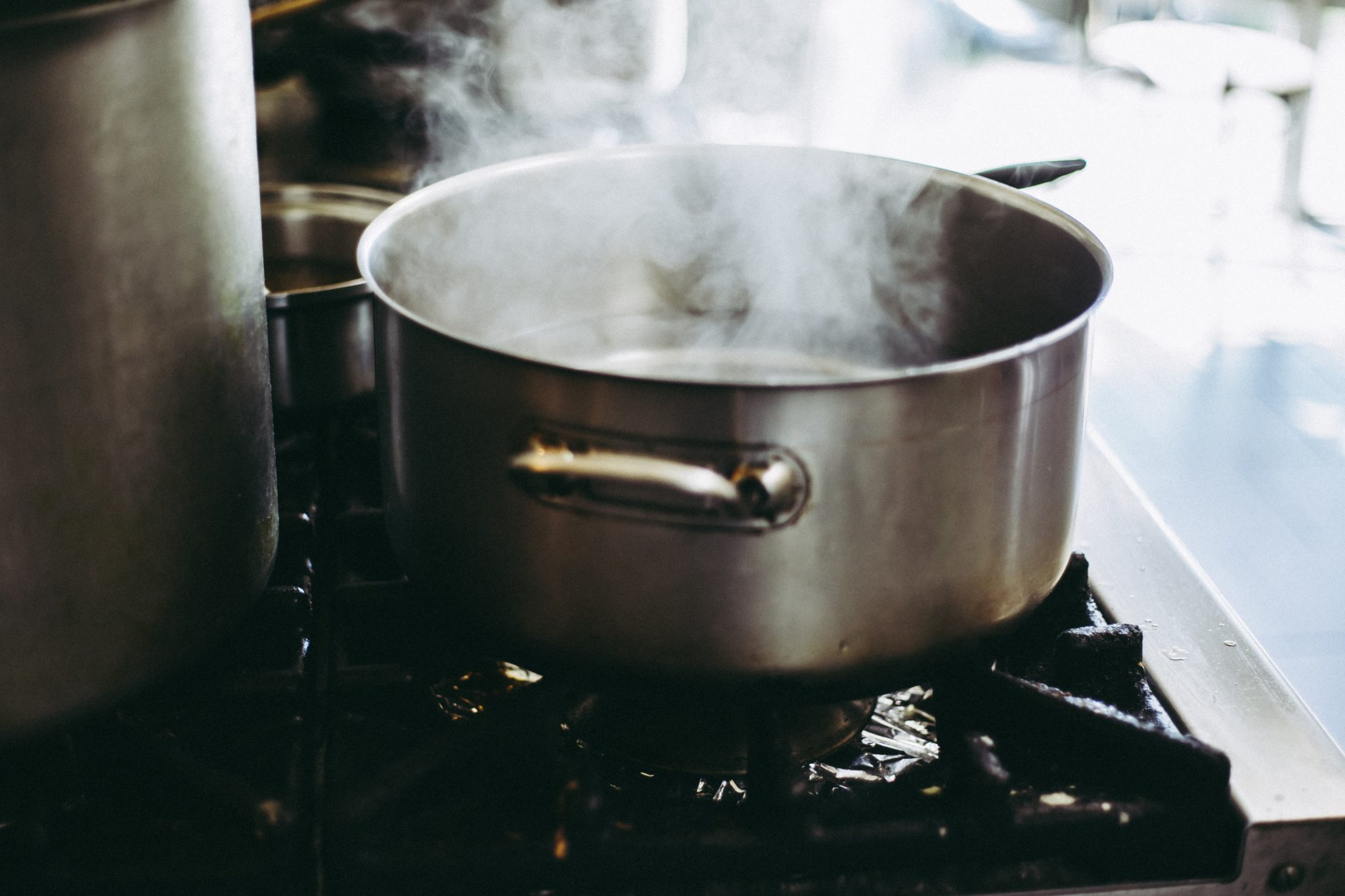 image of a large silver pot on a stove with steam coming out