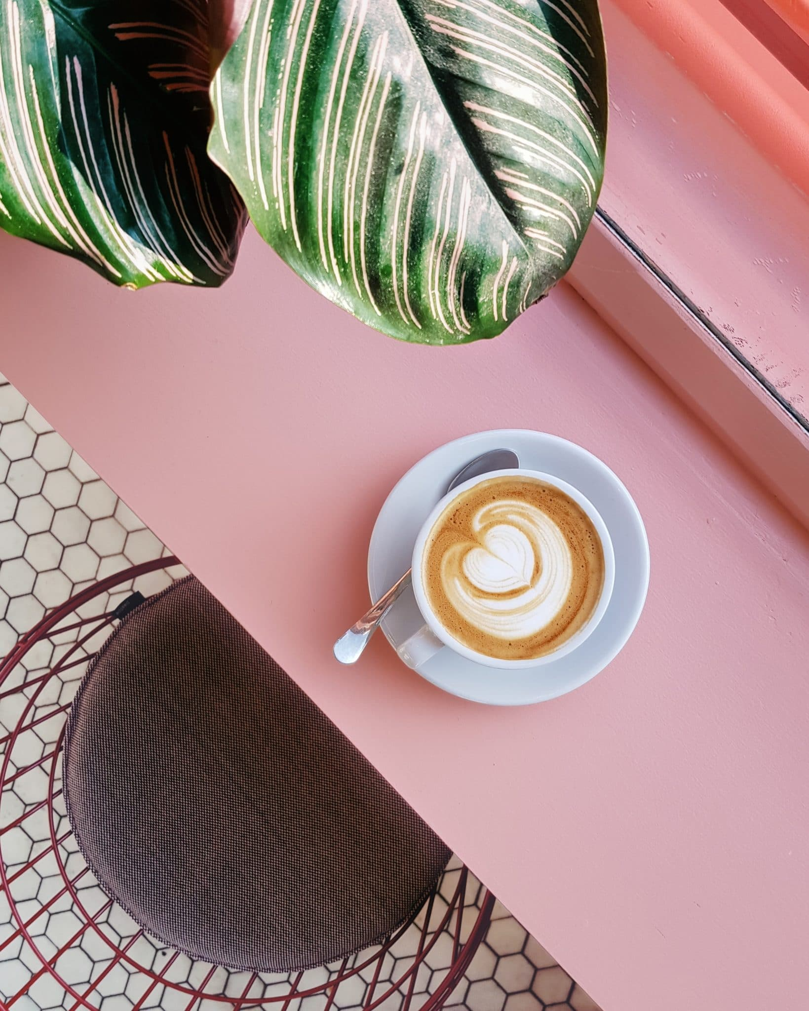 birds eye image of a small mug of coffee on a light pink table next to a grey chair with a green plant in the top left corner