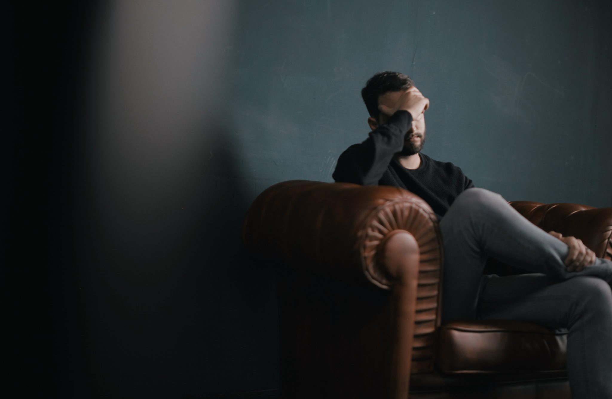 an emotional man sitting on a couch during a therapy session